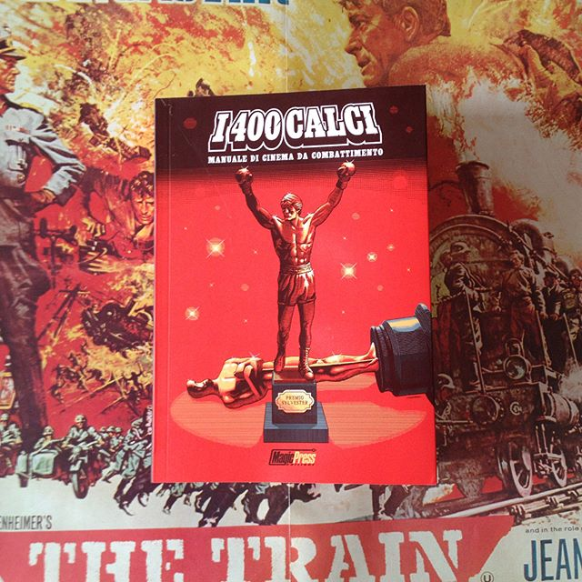 "Finally got a copy of this, stoked with the non #pantone red in print result. Glad surprise also the unexpected closeup of my #Rocky figure in the inside layout! Yay! 🍻 - Background badassness courtesy of #Frankenheimer 's masterwork ""The Train"" poster. #i400calci #stallone #book #academyawards"